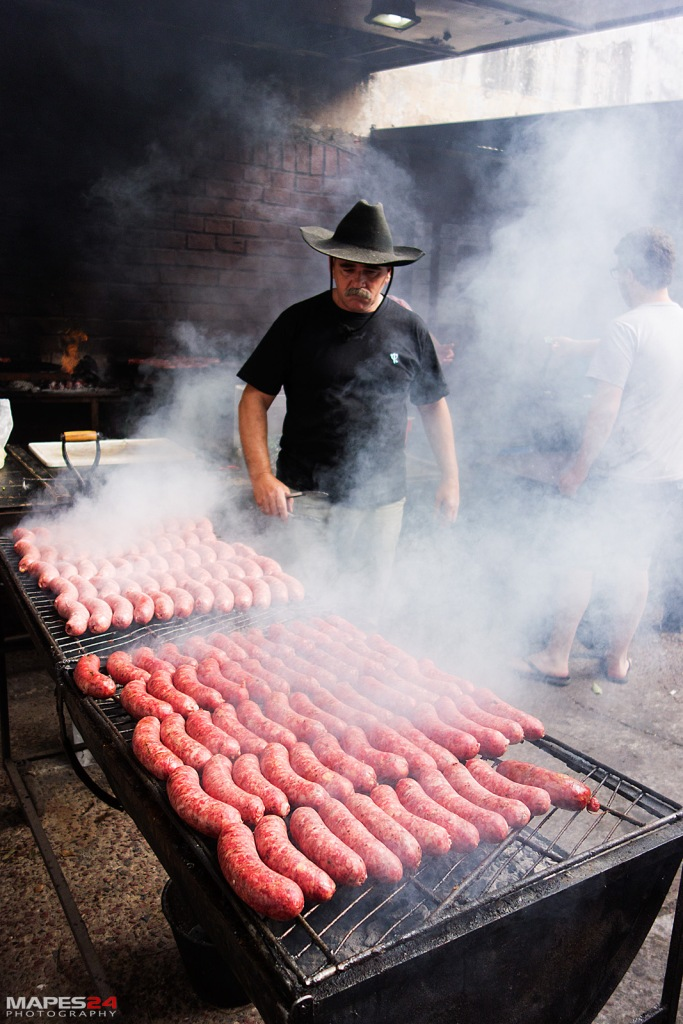 grillmaster cooking chorizo for choripan in san telmo market buenos aires argentina