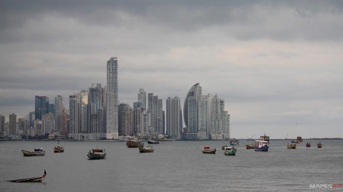 fishing boats in panama city harbor against cityscape